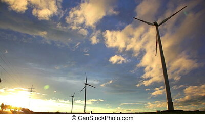 Sunset view at wind turbines under evening sun