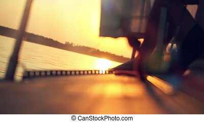sunset view from nose of yacht and sun reflected in water like blurred bokeh and resting traveler