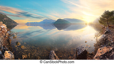 Sunset view from rocky shore of mountain lake