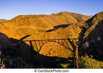 Sunset view of mountains on the Pacific Coast in the Big Sur region; Bixby Creek bridge shadow visible on the side of the valley; California