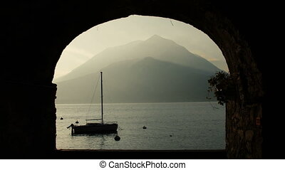 Boat on Lake Como at the sunset, mountain in the background, view through arch. Varenna, Lake Como, Italy.