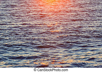 Sunset view of the sea surface at summer time.