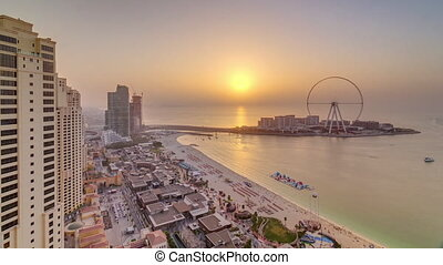 Sunset waterfront overview Jumeirah Beach Residence JBR skyscrapers skyline aerial timelapse with yacht and boats. Shops, restaurants and other entertainment from above