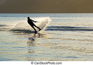 At sunset a Waterskier sprays water into air as he changes direction, on Pittwater, New South Wales, Australia