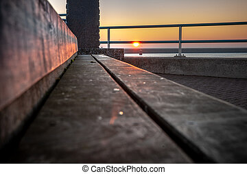 Sunset with a view of the Wadden Sea from a wooden bench
