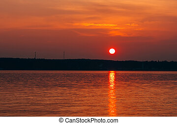 sunset with big red sun over the water of sea