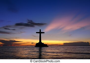 Colorful sunset over Sunken Cemetery on the tropical island of Camiguin. The cross in the sea is a memorial for the victims of the 1871 volcanic eruption here, when the ancient capital Cotta Bato was destroyed by the lava.
