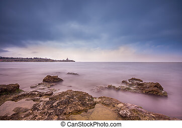 Sunset with dramatic sky, on a rocky coast