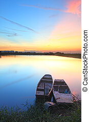 Sunset with isolated boats in water body