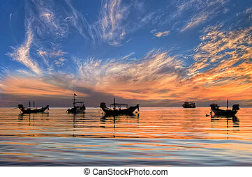 Sunset with longtail boats on tropical beach. Ko Tao island, Thailand.