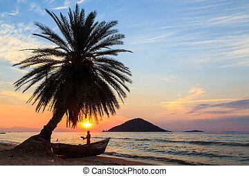 Sunset with palm tree and boat at the beach