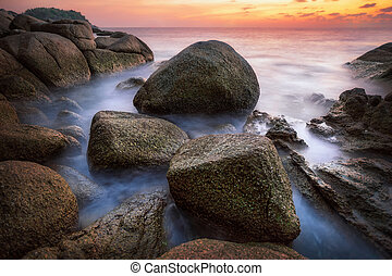 Sunset with rock and beach in Phuket