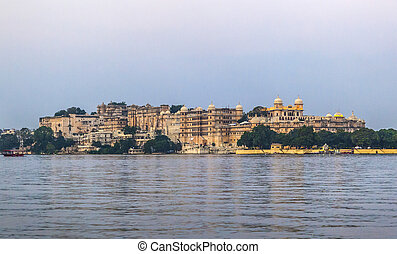 Sunset with view to the city palace in Udaipur with lake pichola