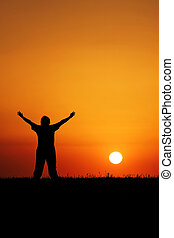 Sunset Worship - A young person with hands in air in front...
