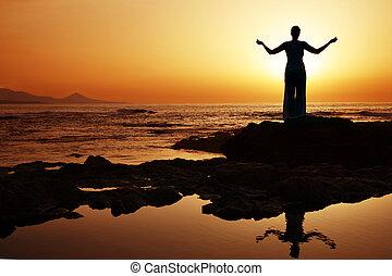 Sunset Yoga - Woman doing yoga at sunset on the seashore
