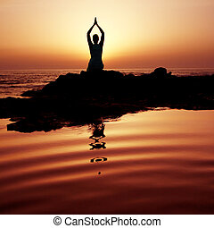 Sunset Yoga - Woman doing yoga at sunset on the seashore