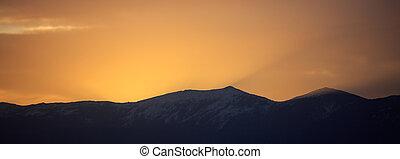 Sunset/sunrise over dark mountains silhouettes