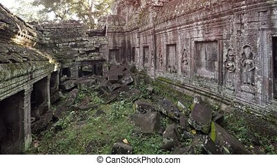 Enormous, hand cut stone blocks, fallen from the tumbledown face of the ancient Ta Prohm temple ruins in Cambodia. Video 3840x2160