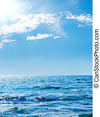 sunshine in blue sky with clouds over sea