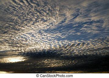 sunshine on a dramatic cloudy blue sky - Sun light passes...