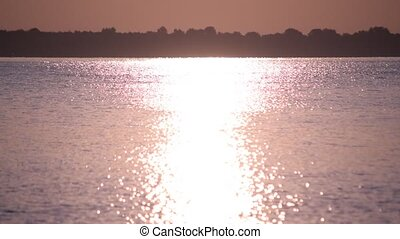 Sunshine reflected in water of lake or river forming a sun path or way of light on water