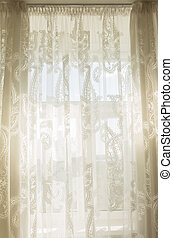 Sunshine through the transparent tulle curtains in room
