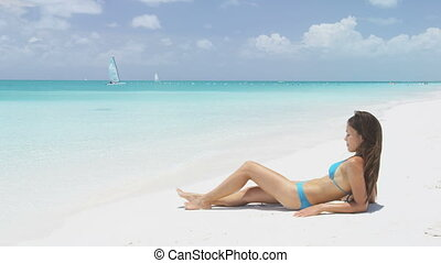 Suntan bikini woman relaxing on beach vacation sunbathing / sun tanning on perfect white sand turquoise beach for summer holidays. Asian model with sexy body and blue swimwear for weight loss concept.