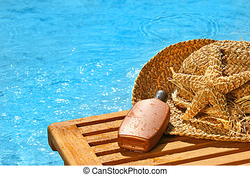 Suntan lotion and straw hat by the pool