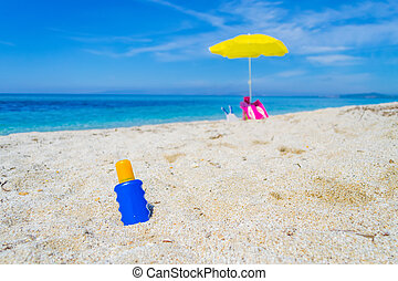 lotion bottle and beach umbrella on the sand