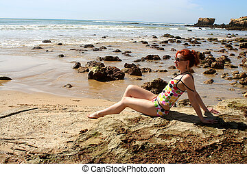 suntanning - woman soaks up the sun at the beach in the...