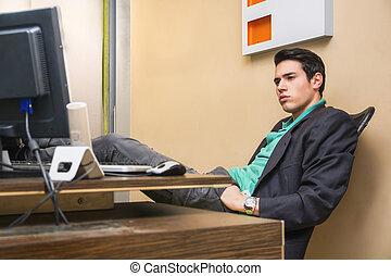 suo, seduta, giovane, serio, scrivania, uomo affari, bello