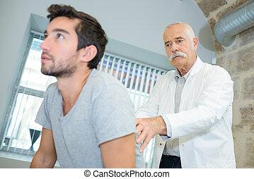 supérieur, docteur, examiner, jeune, dos, homme mûr