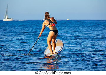 SUP Stand up Surf girl with paddle in a blue ocean sea