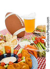 Table set with snack foods for a Super Bowl party. (focus on football) Vertical view with white background.