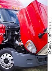 Super bright red modern semi truck engine under open hood -...