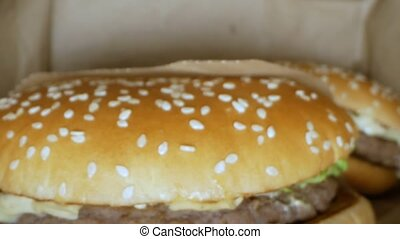 super close-up. hamburger with sesame seeds inside a paper ...