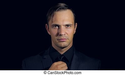 super close-up of a man in black clothes on a black background. 4k. Slow motion.