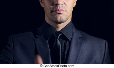 super close-up of a man in black clothes on a black background. 4k. Slow motion. man shows thumbs up. sign super
