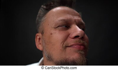 Super close-up of the head of a man with no confidence and looks up. Studio shot isolated on black background. High definition footage.