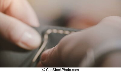 Super close-up shot of skilled artisan hands sewing a...