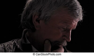 Super close up. Thoughtful grey haired senior man looking down then on camera and wink, camera slide in wearing jacket in semi lit light studio isolated on black background. Prores 422.