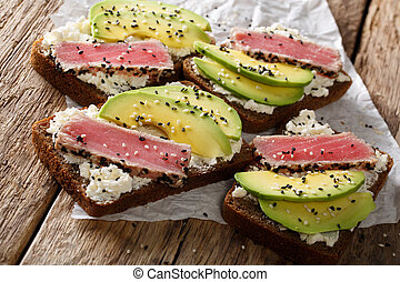Super food: sandwiches with tuna steak in sesame, avocado and cottage cheese close-up. Horizontal