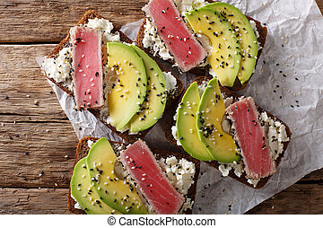 Super food: sandwiches with tuna steak in sesame, avocado and cottage cheese close-up. Horizontal top view