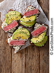 Super food: sandwiches with tuna steak in sesame, avocado and cottage cheese close-up. Vertical top view
