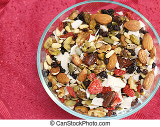 Glass bowl of healthy fruit and nut variety mix of strawberry, blueberry, black currants, dates, pumpkin seeds, pine nuts, almonds, coconut, walnuts, pistachio, raisins, sesame seeds, and pine nuts.