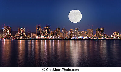 Super full moon over Honolulu downtown at night