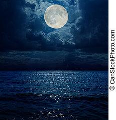 super moon in dark clouds over sea