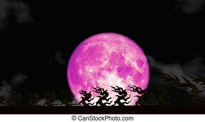 Super pink Strawberry moon back on night sky and blur dark cloud moving pass on the roof