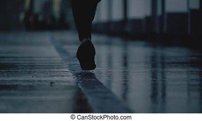 Super slow motion close-up shot of female runner's feet running on wet pavement after rain