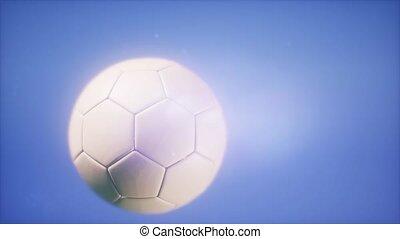 Super slow motion flying soccer ball on blue sky background